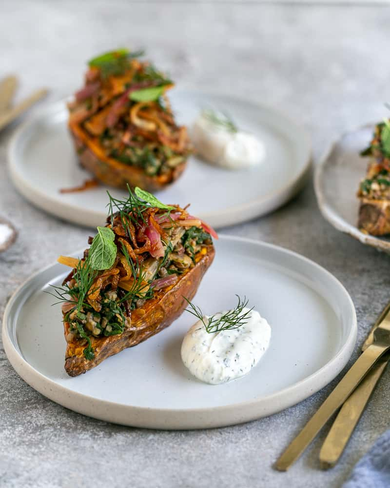 Baked Sweet Potato with Lentils and Swiss Chard served in a plate with labneh on the side