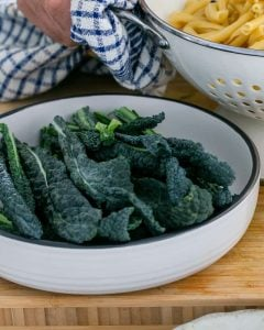 Cut kale in a white bowl for Casarecce Pasta with Asparagus, Kale and Garlic