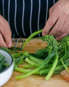 Peeling broccolini stem with a peeler for Casarecce Pasta with Asparagus, Kale and Garlic dish