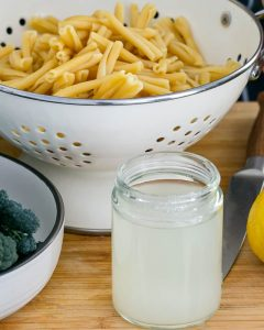Pasta cooking water in a jar with cooked pasta in a strainer in the background