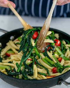 Tossing Casarecce Pasta with Asparagus, Kale and Garlic with two wooden spoons in the pan