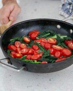 Cut red tomatoes in hot pan with kale, broccolini and asparagus