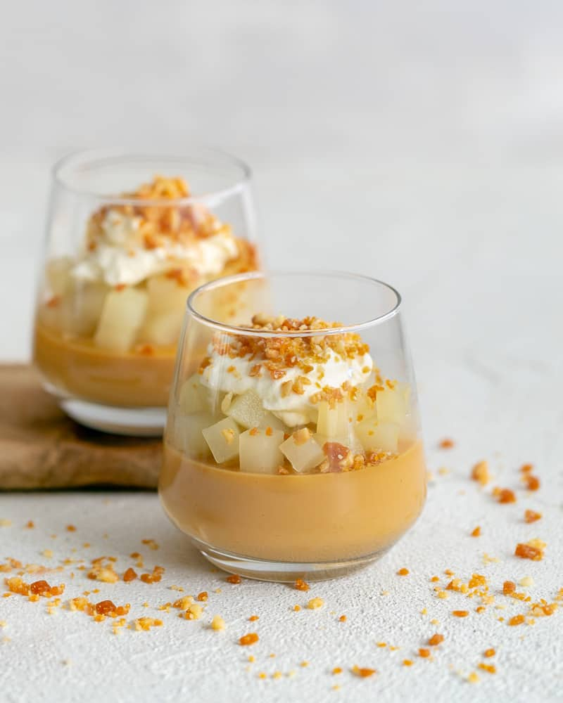 caramel pots with poached pears, whipped cream and macadamia crumble in a glass
