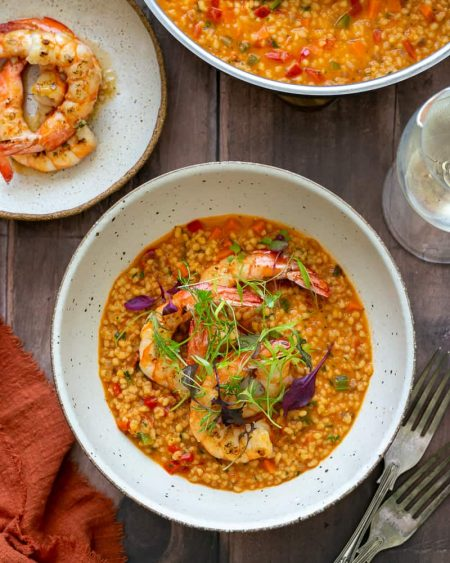 Garlic roasted prawns with fregola sarda individually plated in a bowl garnished with prawns and herbs