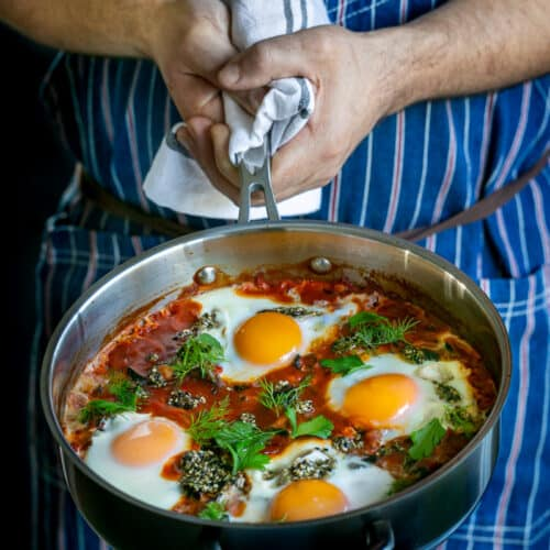 Chef showing freshly cooked Kale Shakshuka with Chickpeas and zataar in a pan