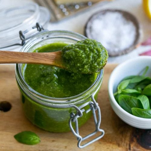 Basil pesto in a jar with a wooden spoon on top with basil pesto in it