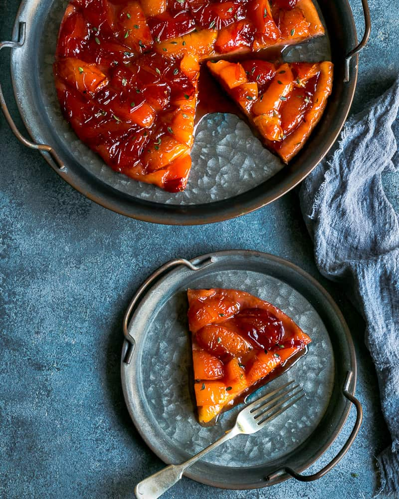 A slice of Plum Tarte Tatin on a vintage metal plate and a fork with the whole tarte tatin the background on a larger vintage metal plate