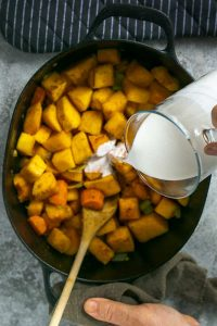 Coconut milk being added to roasted vegetables in stew pot