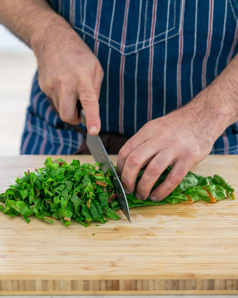 A person chopping the swiss chard leaves in stripes to make Baked sweet Potato with Lentils and Swiss Chard