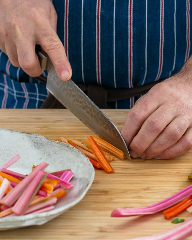 A person chopping stems of the swiss chard to make Baked sweet Potato with Lentils and Swiss Chard