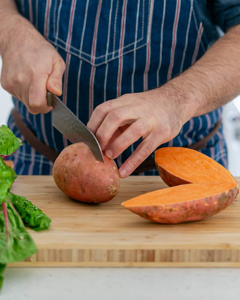 A person cutting Sweet Potato to make baked sweet potato with lentils and swiss chard