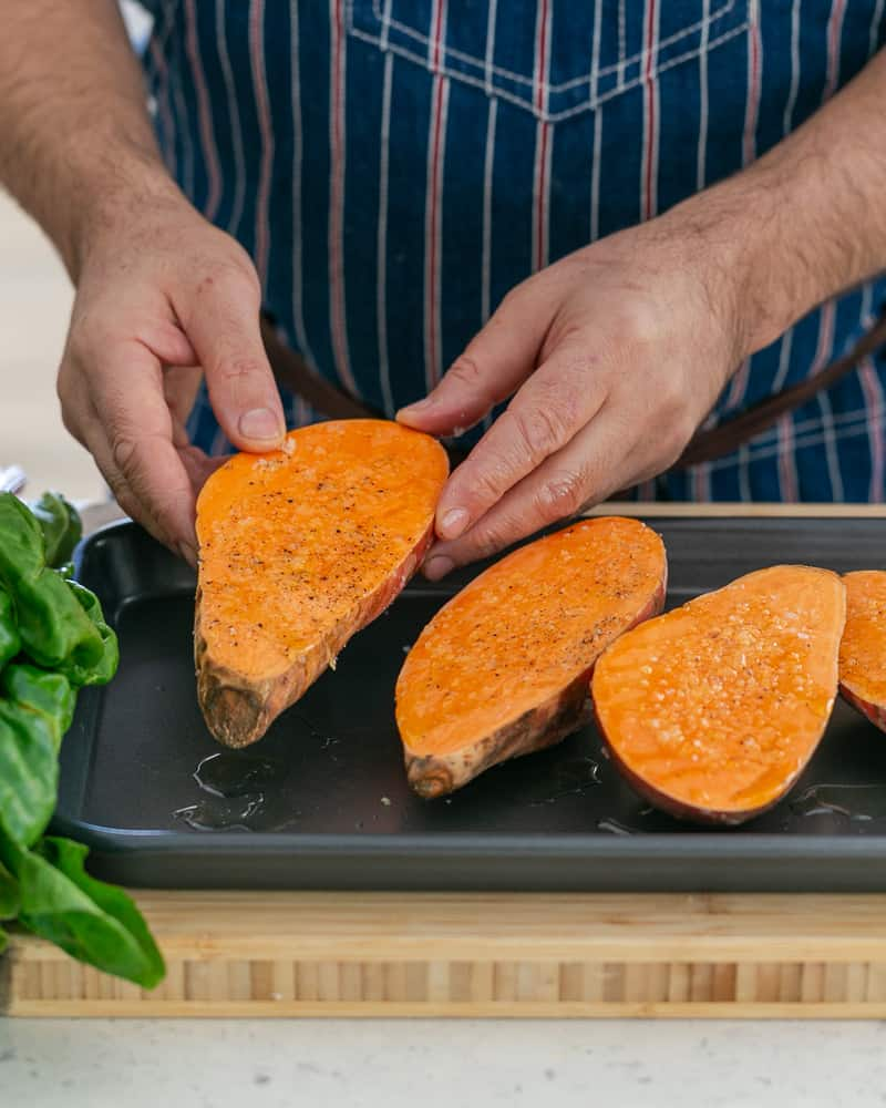 A person arranging the prepared the seasoned sweet potatoes on a baking tray to make Baked sweet Potato with Lentils and Swiss Chard