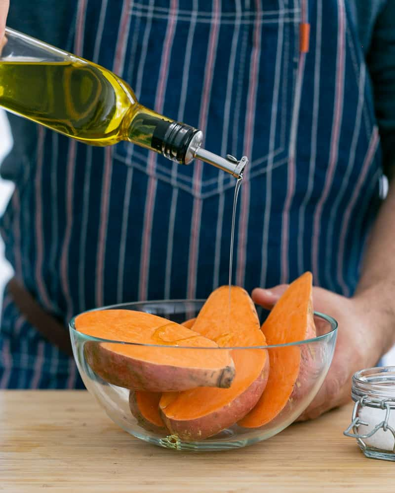 A person putting olive oil on cut Sweet Potato to make baked sweet potato with lentils and swiss chard