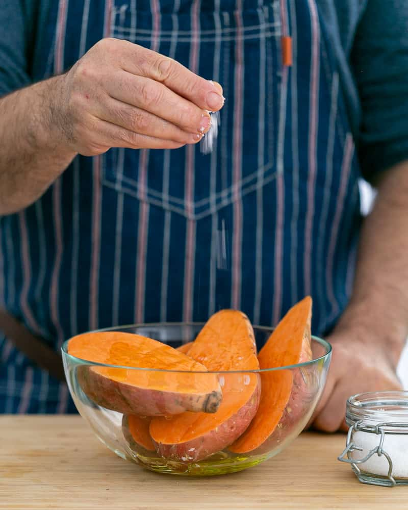A person adding sea salt to cut sweet potatoes to make Baked sweet Potato with Lentils and Swiss Chard