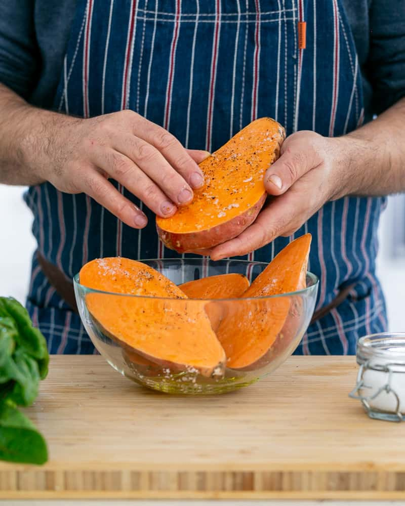 A person seasoning sweet potatoes to make Baked sweet Potato with Lentils and Swiss Chard