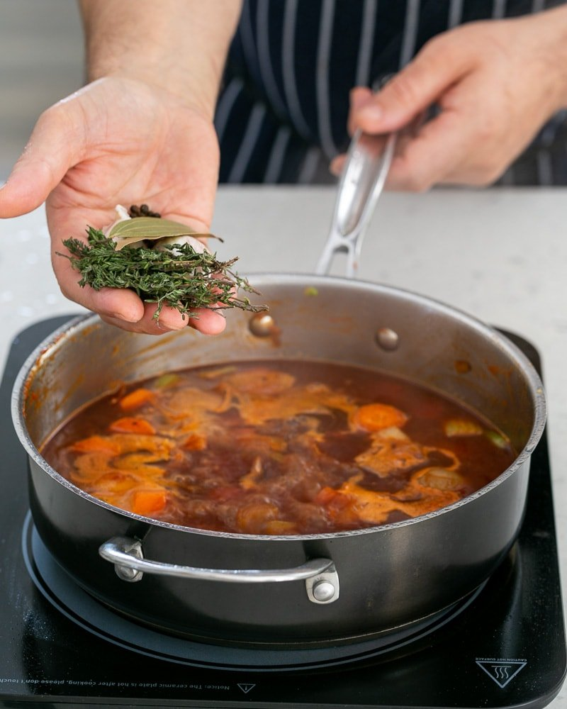 Adding whole spices to cooking jus in pan