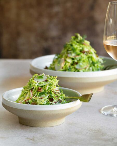 Brussels sprout slaw with raisins served in a big and small bowl with a glass of rose on the side