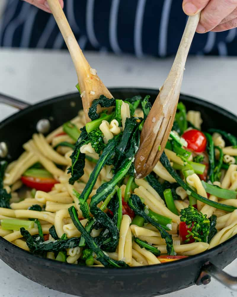 Tossing pasta in a pan with two wooden spoons