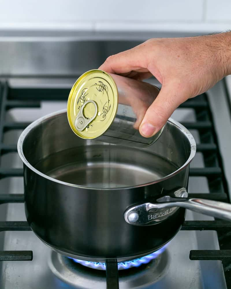 Immersing can of condensed milk in boiling water
