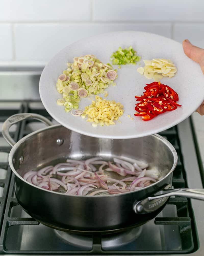 Searing sliced onions with other ingredients in a pan to make the coconut curry sauce