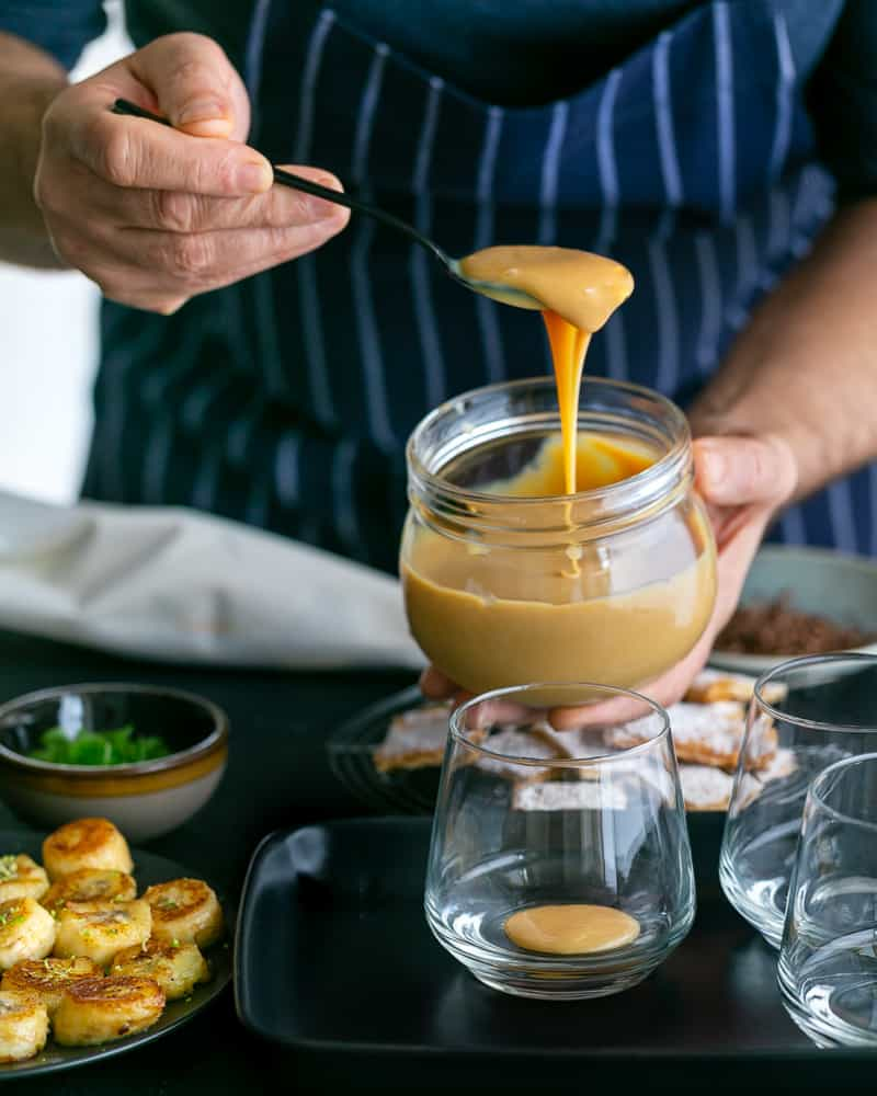Adding a spoonful of the Dulche de leche at the bottom in the glass to assemble Dulce de Leche Verrine with Banana and whipped Cream