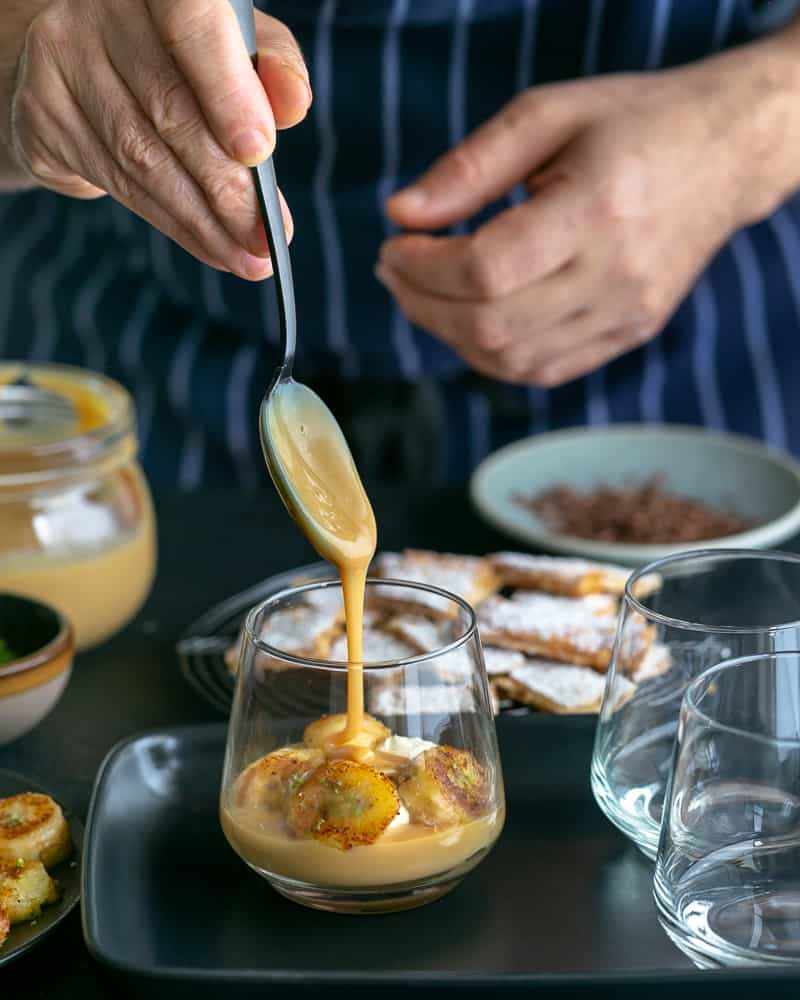 Adding a spoonful of the dulche de leche with a swirl on top of the caramelized bananas in glass