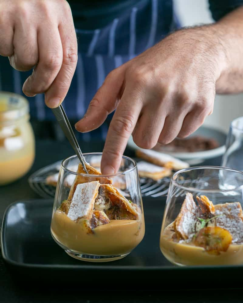 Adding puff pastry chard to assemble Dulce de Leche Verrine with Banana and whipped Cream
