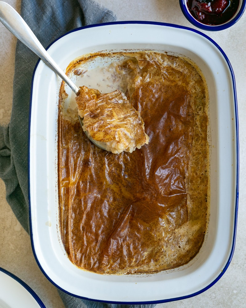 French Baked Rice Pudding with a spoon in the baking dish