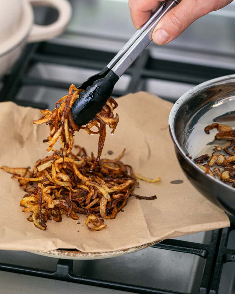 Fried onions to be used as topping for Chopped garlic added to brown lentils in pan to make Baked sweet Potato with Lentils and Swiss Chard