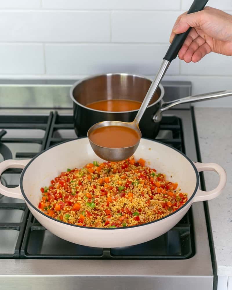 Adding prawn stock to cook fregola sarda and vegetables in the pan