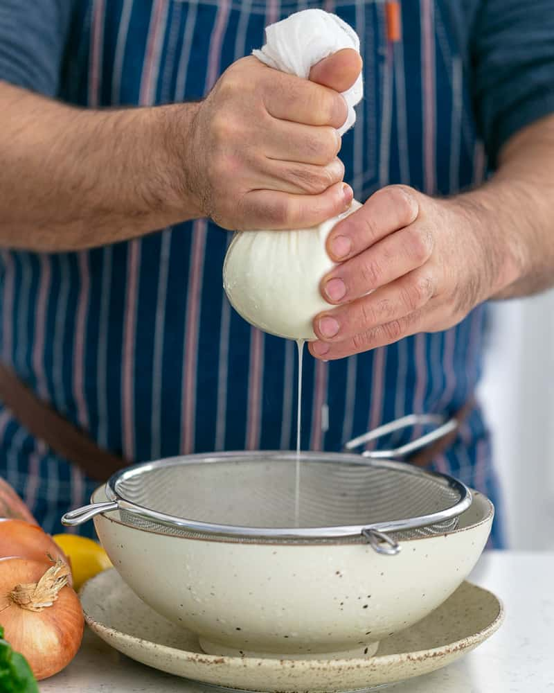 A person making labneh by squeezing out the whey from the yoghurt