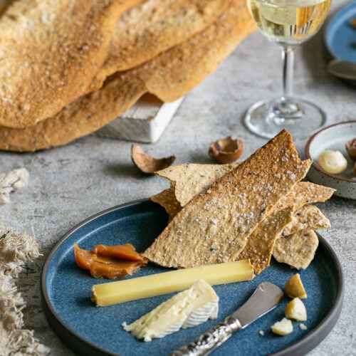 Spiced lavosh crackers served in a plate with cheese and wine