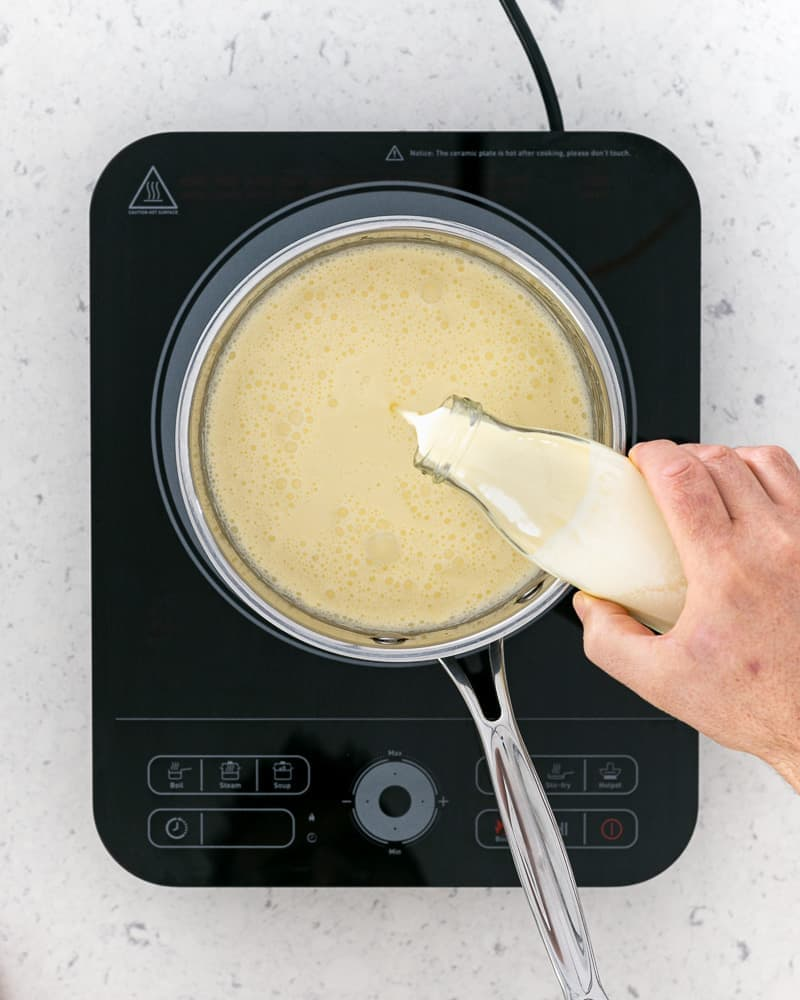 pouring cream into a pot on an induction