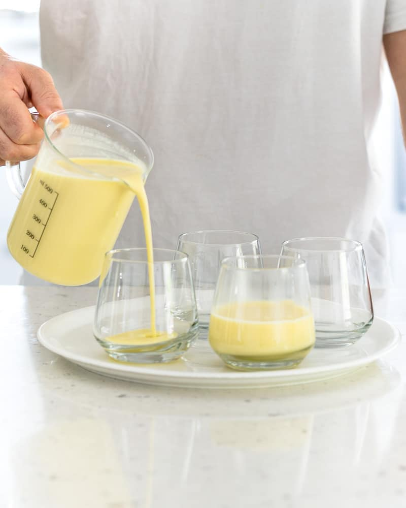 Person pouring the posset mixture into glasses