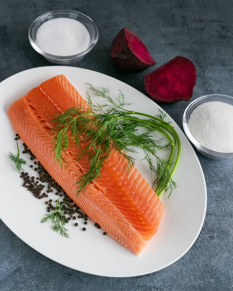 Ingredient for Beet cured salmon gravadlax. Showing salmon, beetroot, sugar, salt, peppercorns and fresh dill