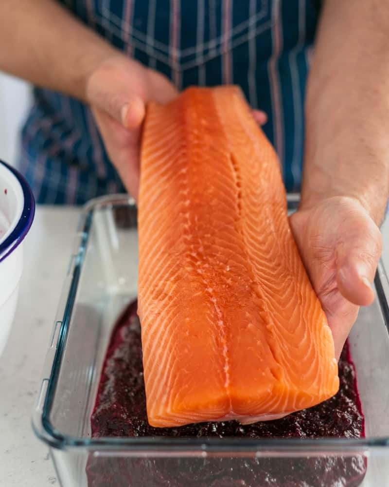 Curing mixture spread at the bottom of a deep glass dish. Also showing salmon being placed in the dish