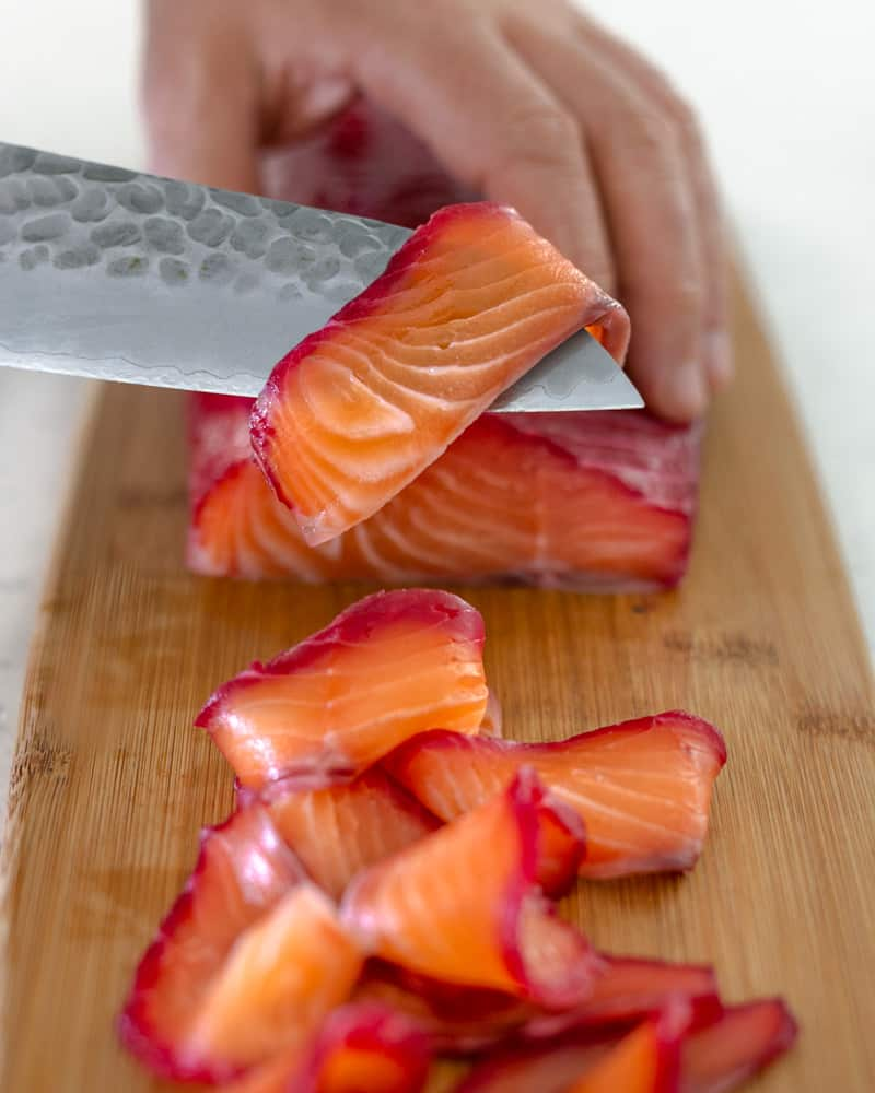 Beet cured Salmon being sliced with a sharp knife on a wooden chopping board