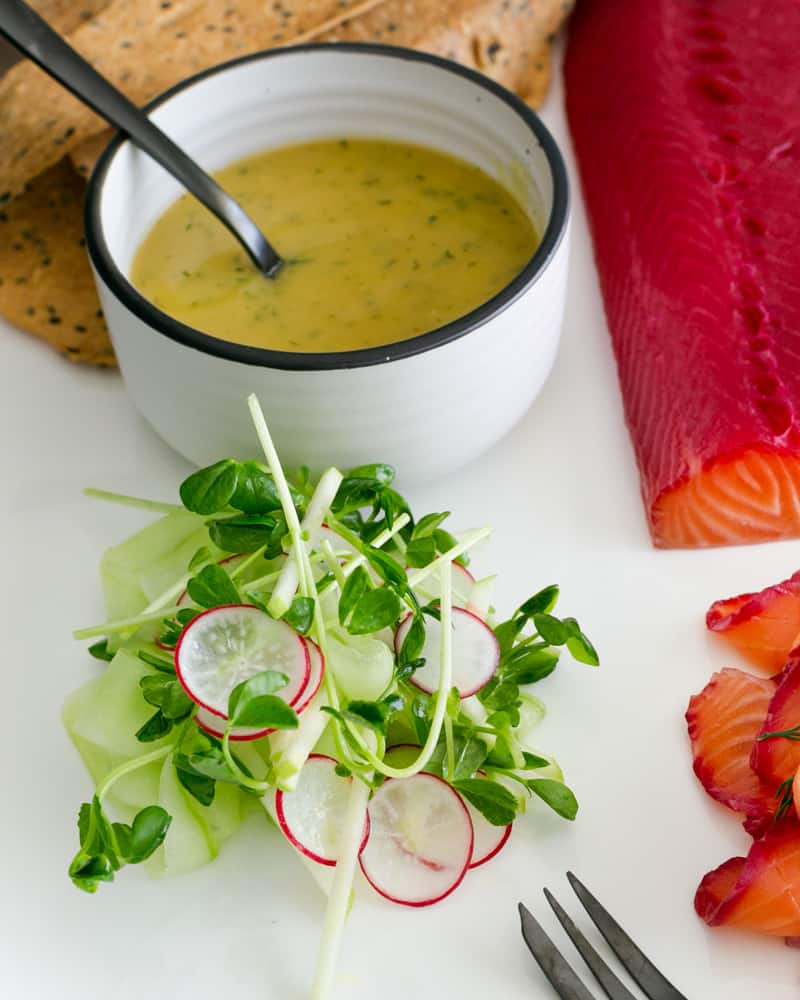 Dressed salad on a white platter with Mustard Dill sauce in a bowl and salmon in the background