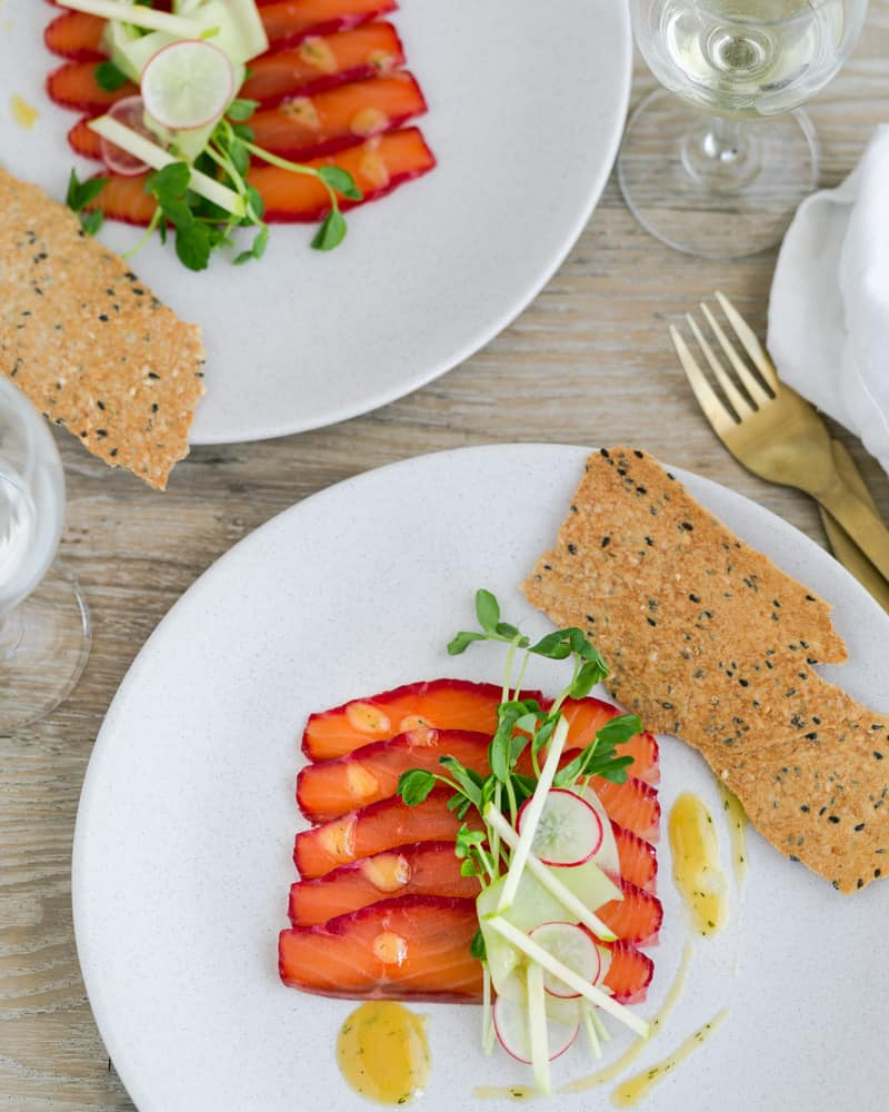 Plated appetizer on a white plate. Thick slices of beet cured salmon served with lavosh cracker, cucumber salad and a drizzle of the mustard dill sauce