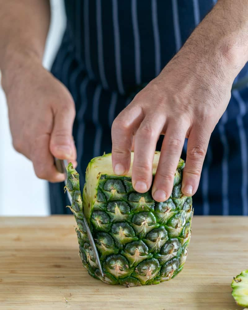 Whole pineapple being peeled with a sharp knife