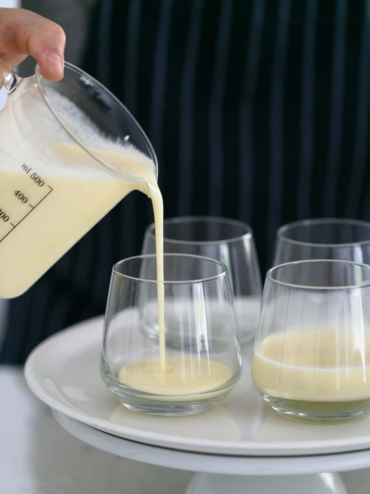 Panna cotta mix being poured into dessert glasses to set
