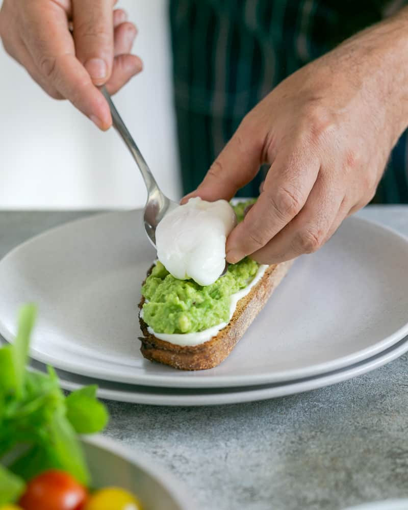 Placing a poached egg on top of avocado mix on toasted sourdough slice