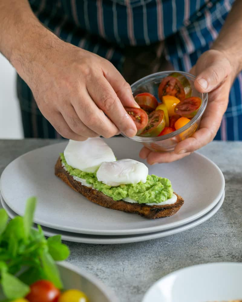 Medley of cut cherry tomatoes being placed around poached eggs on the slice of toasted sourdough bread
