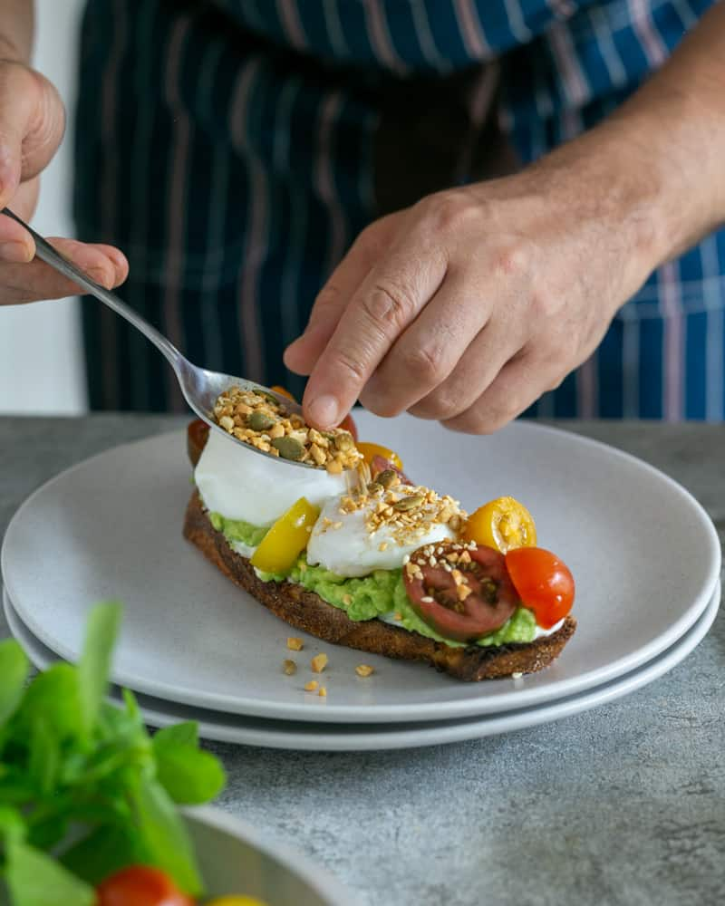 Sprinkling dukkah with a spoon on top of poached eggs and tomatoes on toasted sourdough