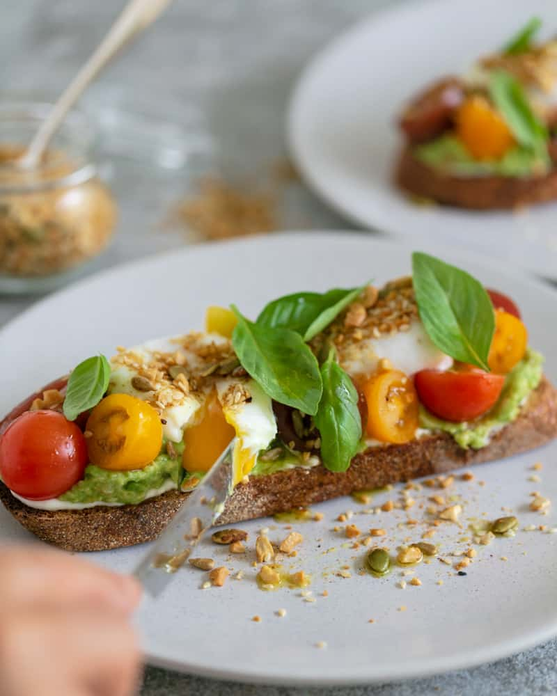 breakfast set up on table with Slice of sourdough with ricotta, crushed avocado, cut poached eggs with yolk flowing, cherry tomatoes, basil and dukkah