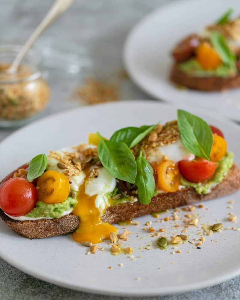 breakfast set up on table with Slice of sourdough with ricotta, crushed avocado, poached eggs cut with egg yolk oozing out, , cherry tomatoes, basil and dukkah