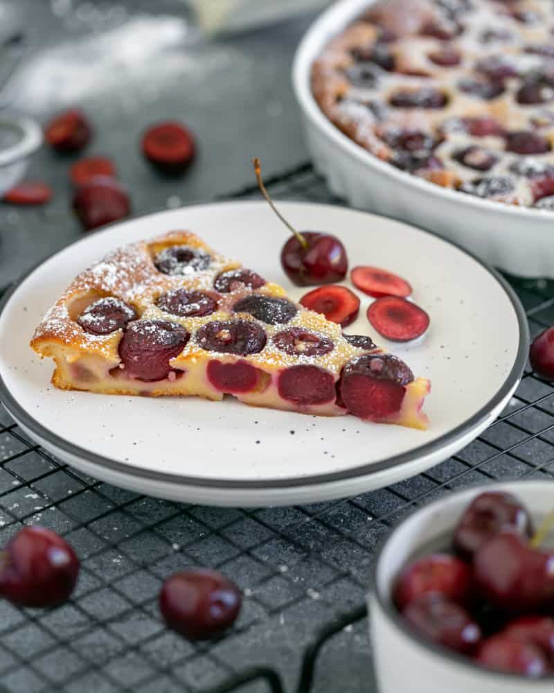 Slice of cherry clafoutis tart on a white plate with cut cherries and a whole cherry on creme fraiche