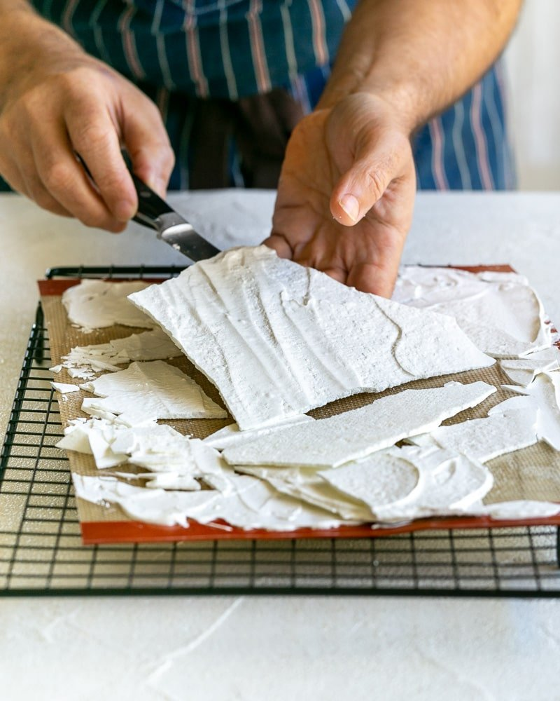 Taking Meringue shards off baking mat with a small knife