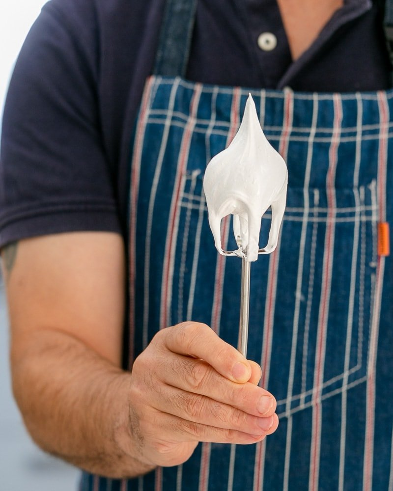 Showing consistency of the beaten egg white mix on a whisk