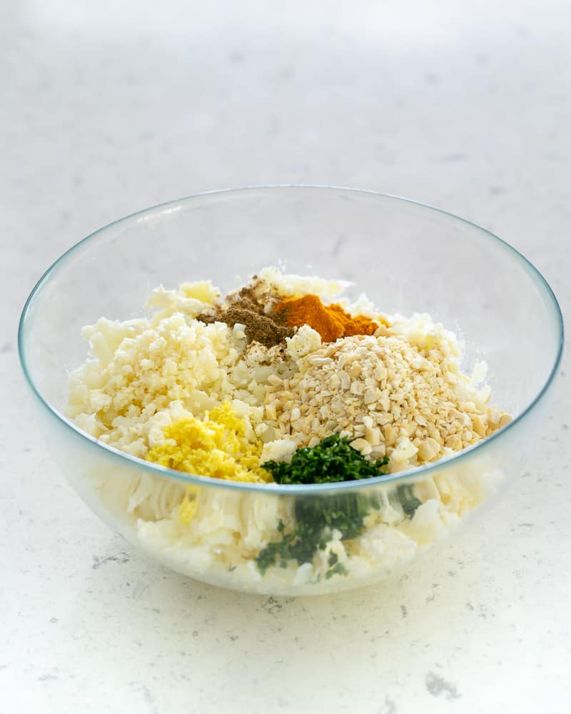 Spices mixed with potato, paneer and besan mixture in bowl